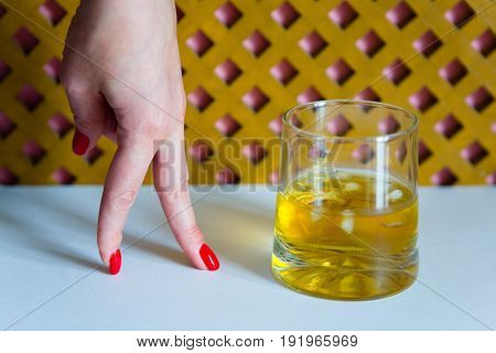 Time of whiskey. A glass of whiskey and a woman's hand with a beautiful manicure.