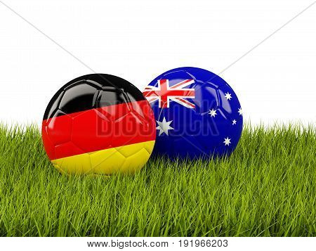 Two Footballs With Flags Of Germany And Australia On Green Grass