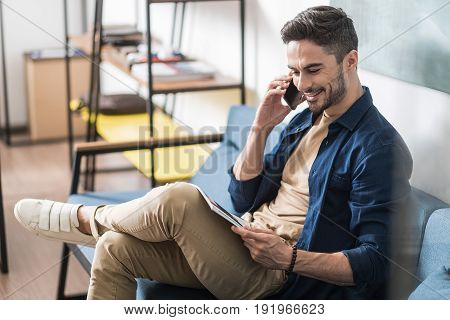 Cheerful young guy with beard is reading magazine and communicating via smartphone. He is sitting on cozy sofa in his settee. Copy space in left side
