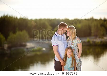 A happy family is resting in the summer near a lake, spending a weekend or a vacation in nature