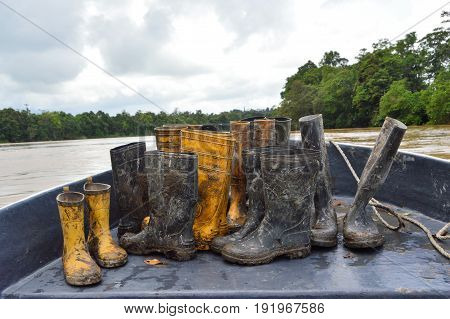 Dirty boots in the boat after rainforest trekking tour