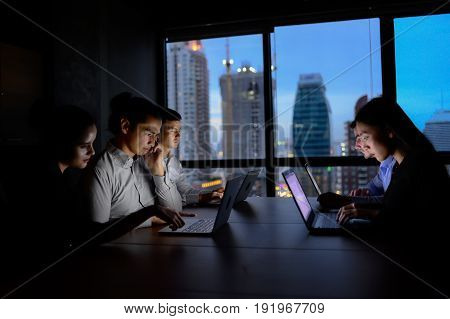 business team working with computer overtime at night and low light. hacker team connect online to other computer pass security firewall and virus scanner .