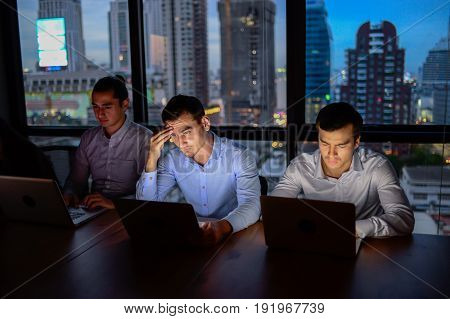 business team three man working with computer overtime at night and low light
