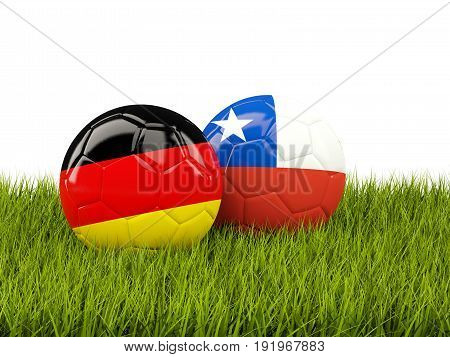 Two Footballs With Flags Of Germany And Chile On Green Grass
