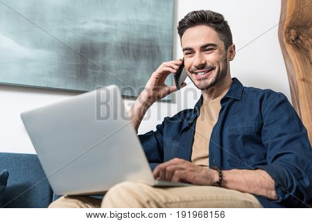 Waist up portrait of cheerful bearded guy sitting on couch and talking through his mobile phone. He is also using laptop lying on his laps. Focus on computer