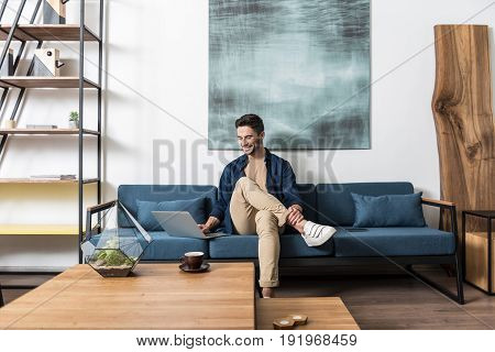 Happy young man is sitting cross legged on couch at his apartment and browsing internet with joy via laptop computer