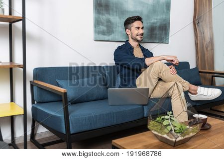 Profile of happy young guy sitting on comfortable sofa in living room. He is having rest after working on laptop computer lying on couch beside him. Copy space in left side