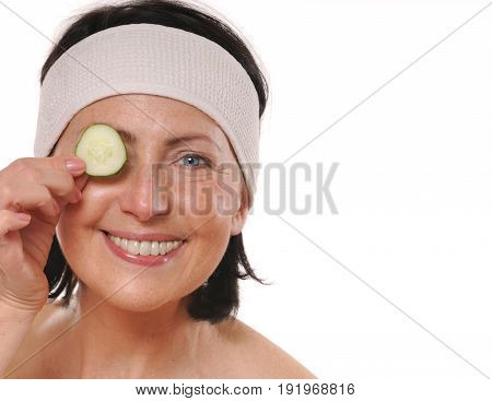 Cheerful mature woman holding piece of cucumber in front of her eye and smile. Natural spa treatment. Isolated on white background