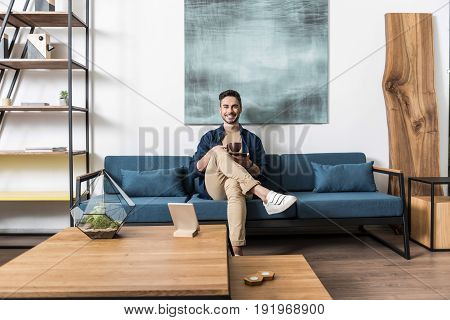 Portrait of happy young man with beard sitting cross-legged on cozy couch and drinking coffee. He is holding cup of coffee in his hands and smiling