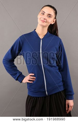 Young hipster girl wearing blank purple cotton zip up sweatshirt with copy space for your design or logo mock-up of ltemplate womens hoodie grey wall in the background