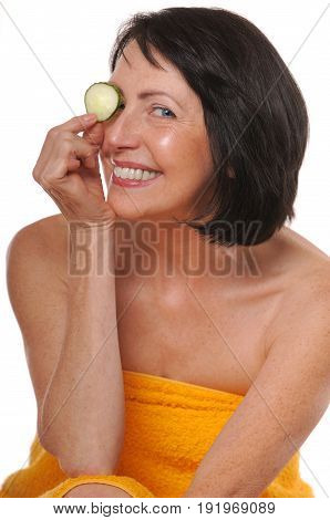 Portrait of happy senior woman with cucumber. Beauty and care concept