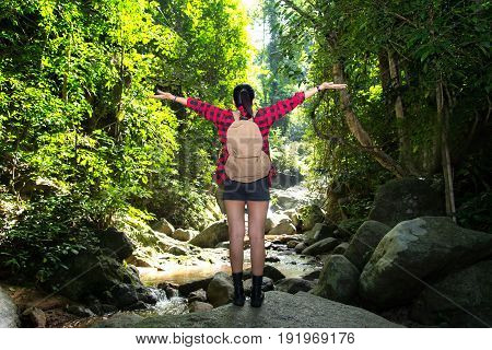 Traveler woman feeling victorious facing on the water fall.