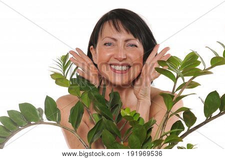 Cheerful happy mature woman peep out from behind the flowers. Natural spa treatment. Isolated on white background
