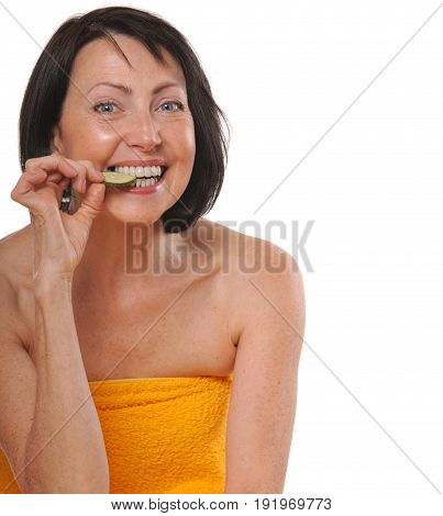 Happy senior woman in spa towel eating piece of cucumber. Beauty and care concept