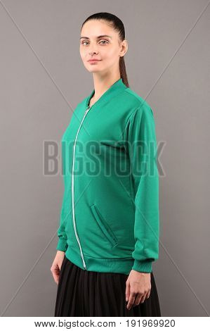 Young hipster girl wearing blank green lime cotton zip up sweatshirt with copy space for your design or logo mock-up of ltemplate womens hoodie grey wall in the background