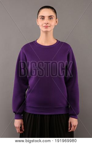 Young hipster girl wearing blank purple cotton sweatshirt with copy space for your design or logo mock-up of purple template womens hoodie grey wall in the background