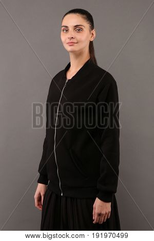 Young hipster girl wearing blank black cotton zip up sweatshirt with copy space for your design or logo mock-up of womens hoodie grey wall in the background