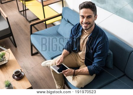 Portrait of jolly young bearded man resting on couch with his tablet in living room. He is sitting cross-legged and smiling. Copy space in left side. Top view