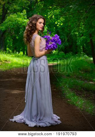 Young woman with flowers in the forest