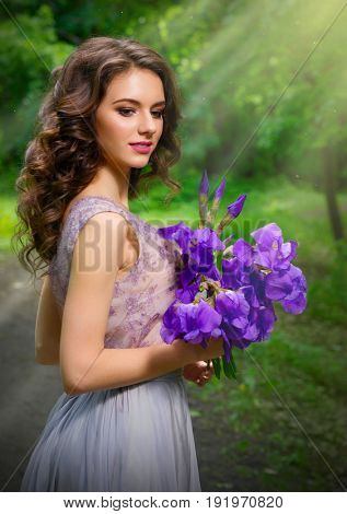 Young woman with flowers in the forest (with sunrays ver)