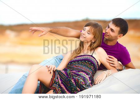 Lovers lying on sand in desert. romantic travel honeymoon vacation summer holidays. young girl dressed in a colorful dress and man in a violet t-shirt. man points at something with his finger