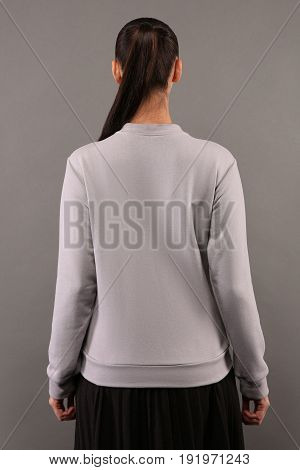 Back of Young hipster girl wearing blank grey cotton sweatshirt with copy space for your design or logo mock-up of ltemplate womens hoodie grey wall in the background