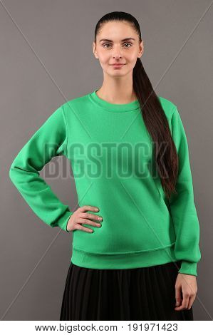 Young hipster girl wearing blank lime green cotton sweatshirt with copy space for your design or logo mock-up of ltemplate womens hoodie grey wall in the background