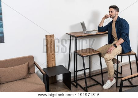 Pensive young guy with beard is sitting on high chair at desk near laptop. He is thinking of his work and looking to distance. Copy space in left side