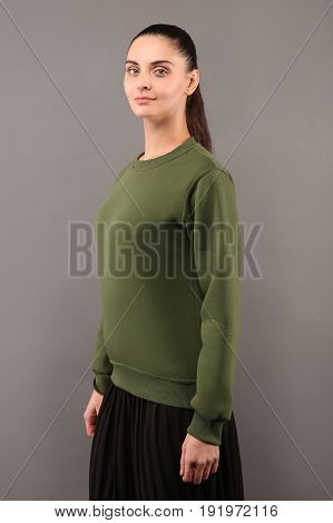 Young hipster girl wearing blank Khaki cotton sweatshirt with copy space for your design or logo mock-up of ltemplate womens hoodie grey wall in the background