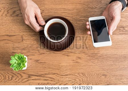Close up of hands of young man sitting at desk and drinking coffee. He is holding smartphone in one hand and sending messages. Top view