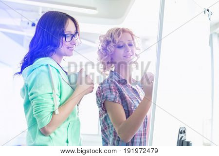 Smiling businesswomen preparing presentation on whiteboard in creative office