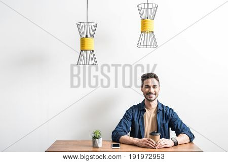 Waist up portrait of joyful bearded young man sitting at desk, smiling and holding special plastic cup with coffee by both hands. Ceiling lamps hanging over workplace. Isolated