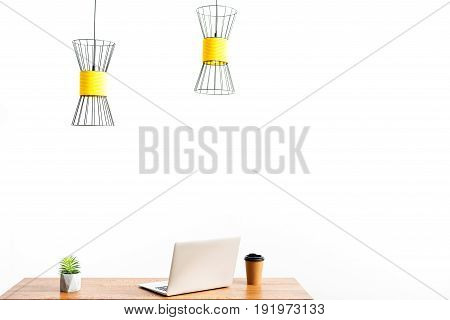 laptop and plastic coffee cup on table. Chandelier hanging over workplace. Isolated and copy space in right side