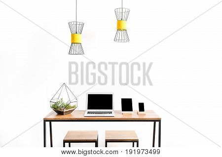 open laptop, tablet and smartphone on desk with two stools. Two yellow chandeliers hanging over working place. Isolated