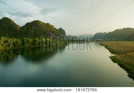 Sunset over tropical river of Phong Nha National Park Village in vietnam, south east asia reflecting water