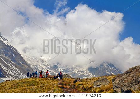 Hikers team on a hill in Himalayan mountains. Nepal, Annapurna region, Annapurna Base Camp track. Mountain Cloudy Landscape. Travel concept.