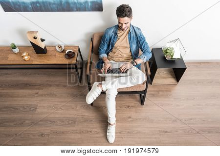 Top view of happy young bearded man sitting cross-legged on comfortable armchair and working with joy on his laptop. He is typing something on keyboard and smiling. Copy space in left side