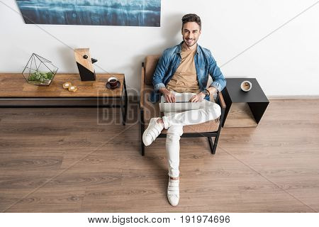 Full length portrait of jolly young man with beard sitting cross-legged on lounger with laptop on his laps. He is typing and smiling. Top view