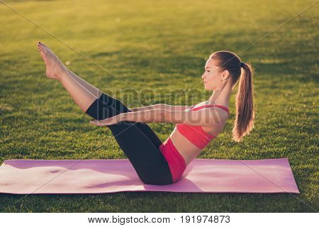 Young Sport Woman Is Making Abs Workout While Practicing Yoga In A Spring Morning Park, Wearing Fash
