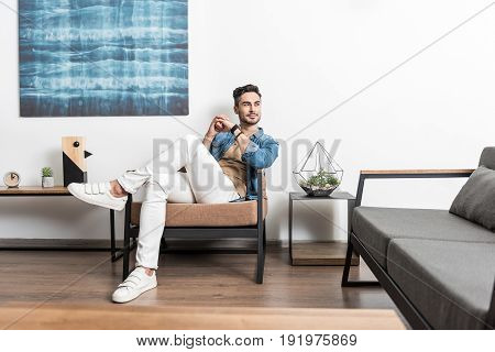 Full length portrait of thoughtful young man with beard sitting cross-legged on lounger in living room. He is keeping his hands together and looking aside