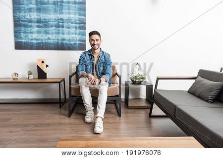 Full length portrait of happy young bearded man sitting on armchair and smiling. He is enjoying his free time in his room