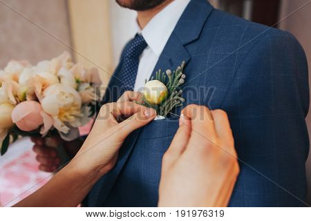 The bride's hand on the groom's shoulder, Boutonniere on a suit, gentle female hand close-up, wedding ring, hugs of a couple
