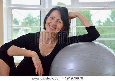 Happy senior woman resting after exercise. Fit aged woman lean on the big gray exercise ball. Close up portrait