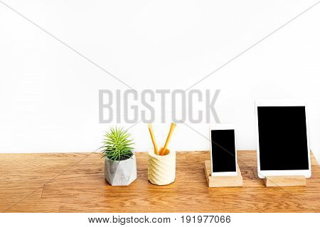 Close up of tablet, smart phone, pen holder and pot with flower on desk top. Isolated