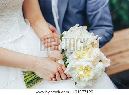 The bride and groom sit side by side and hold a wedding bouquet in their hands. close-up