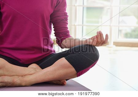 Mature woman sitting on the floor in lotus position. Healthy fitness concept with active lifestyle. Close up