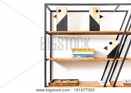 Close up of metallic storage unit with wooden shelves, pile of books and decorated birds and other household thing on them