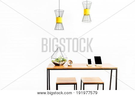 Close up of tablet with smartphone, flowerpot and alarm clock on table with two stools. Lusters hanging over working place. copy space in left side