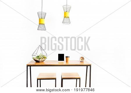 Close up of tablet with plastic cup for coffee, alarm clock and flowerpot on long table with stools. Chandeliers hanging over working place. Isolated