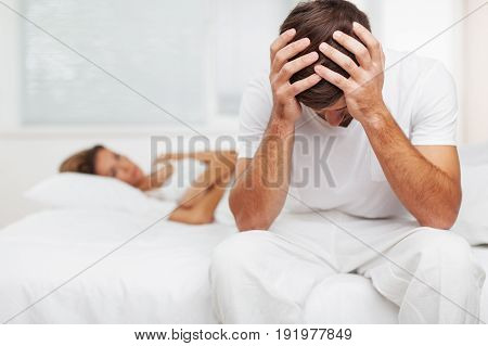 Sitting man bed woman laying hands on head white